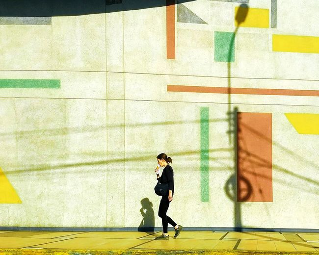 Side view of a man walking against wall