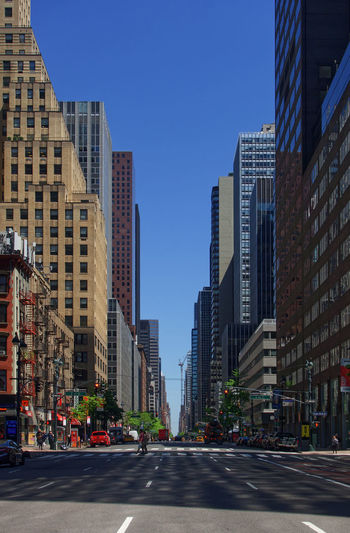 City street and buildings against clear blue sky