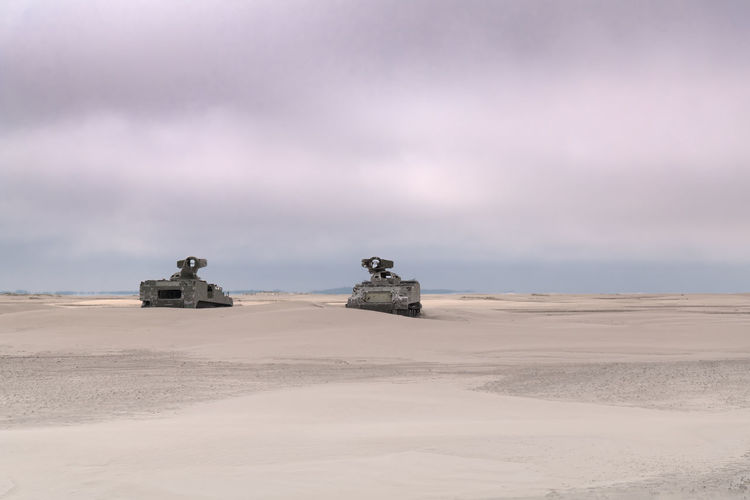 2 army vehicles on the beach tanks