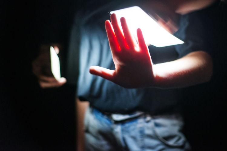 Close-up of human hand on illuminated mirror