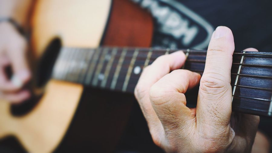 Close-up of person hand playing guitar