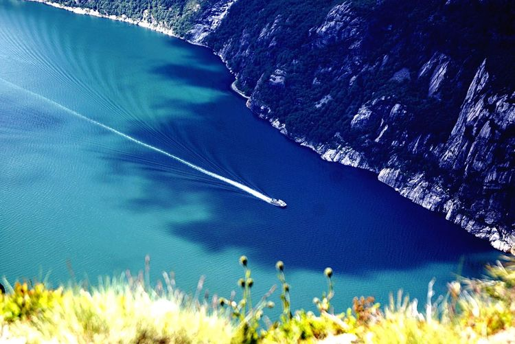 High angle view of boat in river by mountain during sunny day
