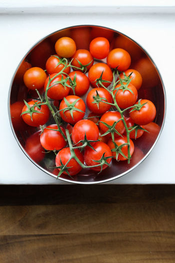 High angle view of cheery tomatoes in bowl on table