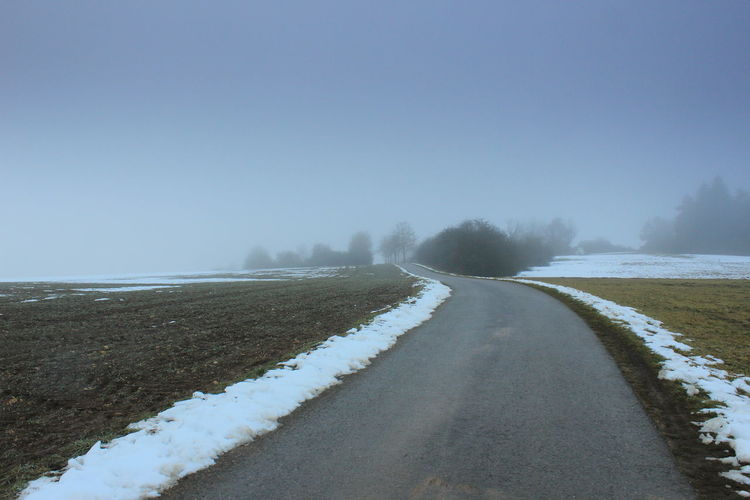 Empty road along snow covered landscape