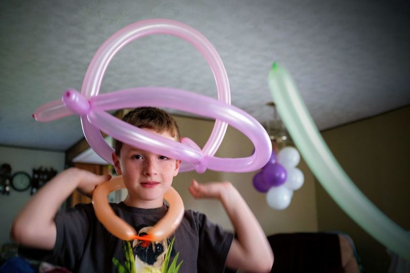Portrait of boy holding balloons at home