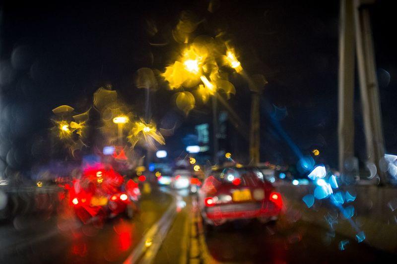 Illuminated cars on road in city at night