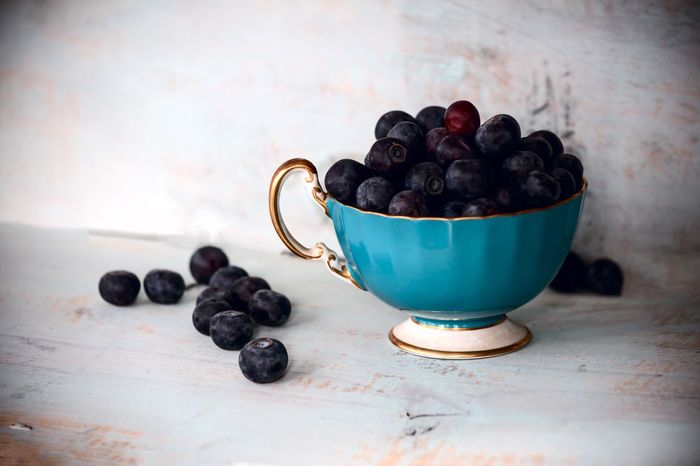 Blueberry background with pile of fresh juicy blueberries in antique tea cup on rustic blue wood table with blueberries and gold rim Healthy Eating Nutriton Diet Background Blueberries Antioxidant Fruit Fresh Breakfast Blueberry Blue Color Food And Drink Freshness Table Healthy Eating No People Indoors  Food Blueberry Fruit Black Color Close-up Day