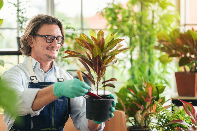 Man taking care of her potted plants at home, gardening, planting at home