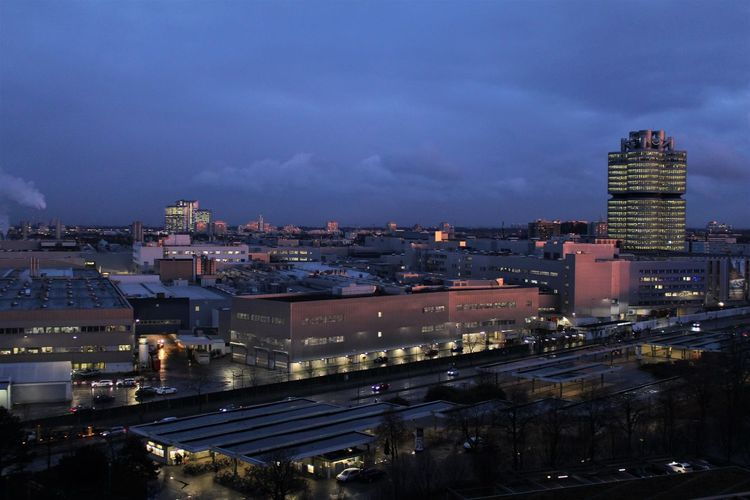 High angle view of illuminated buildings in city at night, the bmw fabric in munich