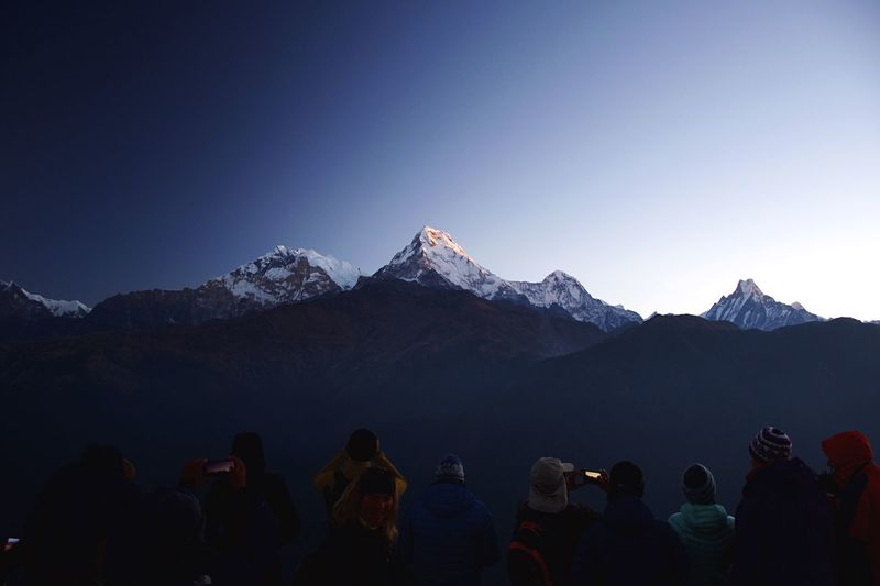 People against snowcapped mountains and clear blue sky