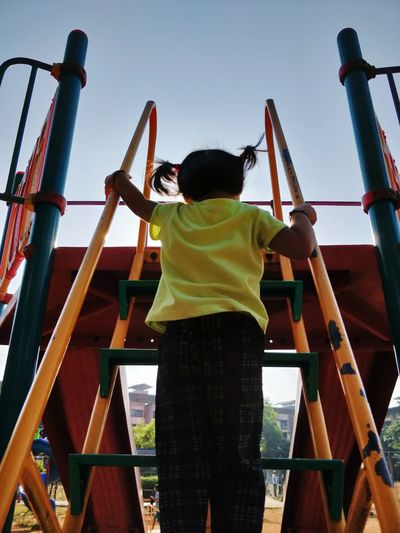 Rear view of girl climbing slide steps in playground against sky