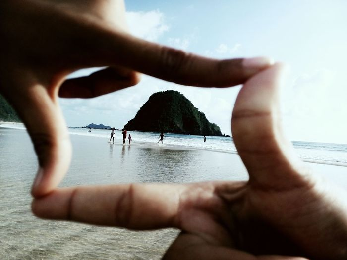 Cropped hands forming shape in front of people at beach