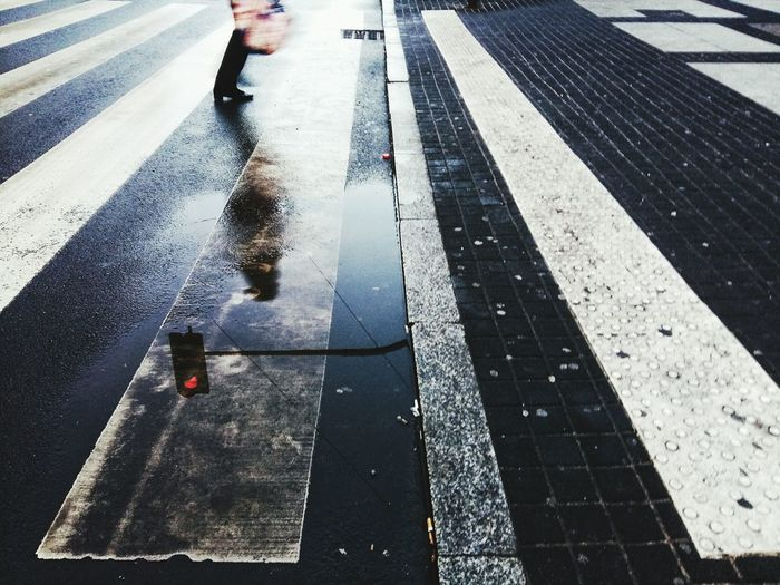 Pedestrian and road signal reflecting in puddle on street