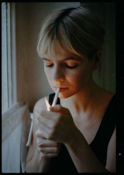 Close-up portrait of young woman holding cigarette