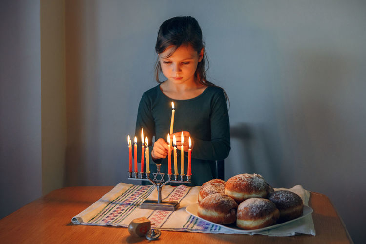Girl lighting candles on menorah for traditional winter jewish hanukkah holiday at home.