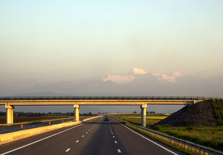 Bridge across the road against the backdrop of the mountains, lit by the setting sun Across Road Setting Transportation Against Beauty In Nature Bridge Clear Sky Day Landscape Lit Mountain Mountain Range Mountains Nature No People Outdoors Road Road Marking Scenics Sky Sun The Way Forward Transportation
