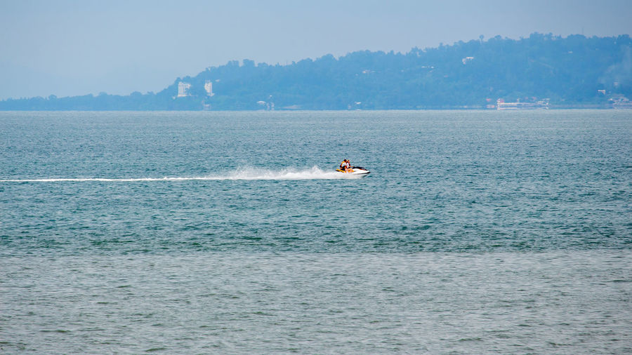 People riding jet boat on sea against sky