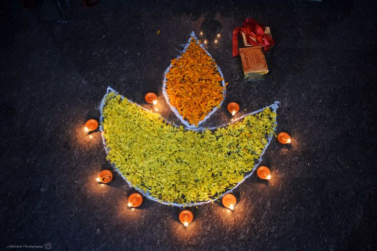 """Diwali,DeepavaliorDipavaliis theHindufestival of lights, which is celebrated every autumn in the northern hemisphere (spring in southern hemisphere).One of the most popular festivals ofHinduism, Diwali symbolises the spiritual """"victory of light over darkness, good over evil and knowledge over ignorance.""""]During the celebration, temples, homes, shops and office buildings are brightly illuminated.[10]The preparations, and rituals, for the festival typically last five days, with the climax occurring on the third day coinciding with the darkest night of theHindu lunisolarmonthKartika. In theGregorian calendar, the festival generally falls between mid-October and mid-November. (wikipedia) Diya - Oil Lamp Flower Petals SweetBox Clicked On Nikon D3300 Rangoli Pattern Creativity Design Close-up Colorful Shape"""
