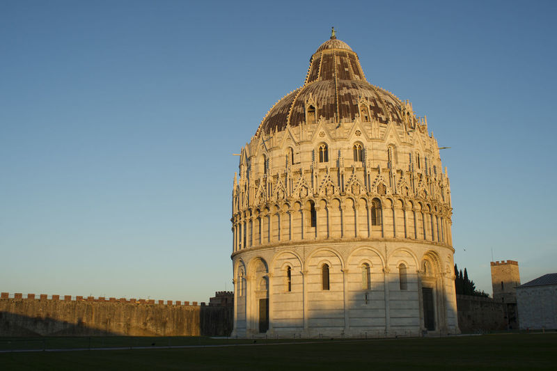 Pisa baptistery on field against clear blue sky in city