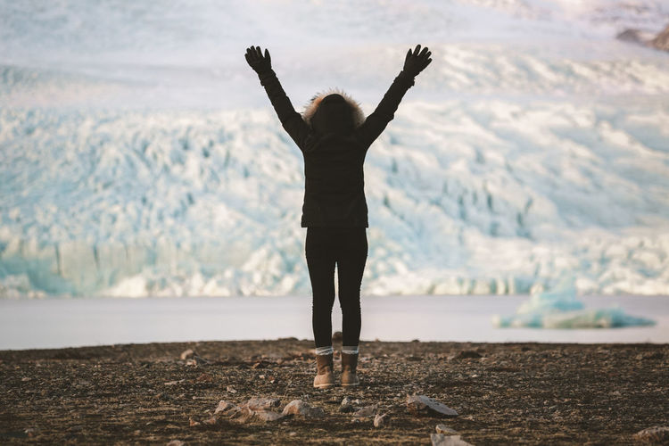 Woman with arms raised standing on landscape against sky