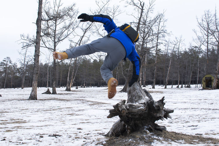Siberia, Russia Winter Cold Temperature Tree Snow Real People One Person Leisure Activity Full Length Lifestyles Motion Day Men Jumping Nature Plant Warm Clothing Mid-air Land Bare Tree Outdoors Human Arm