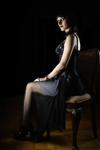 Young woman sitting on chair against black background