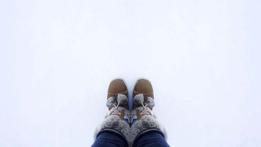 Low Section Of Person Wearing Snow Boots During Winter