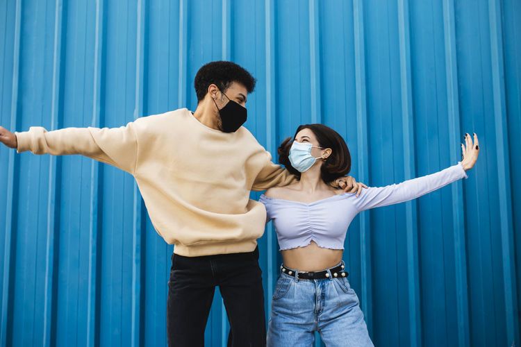 Young couple standing against blue curtain