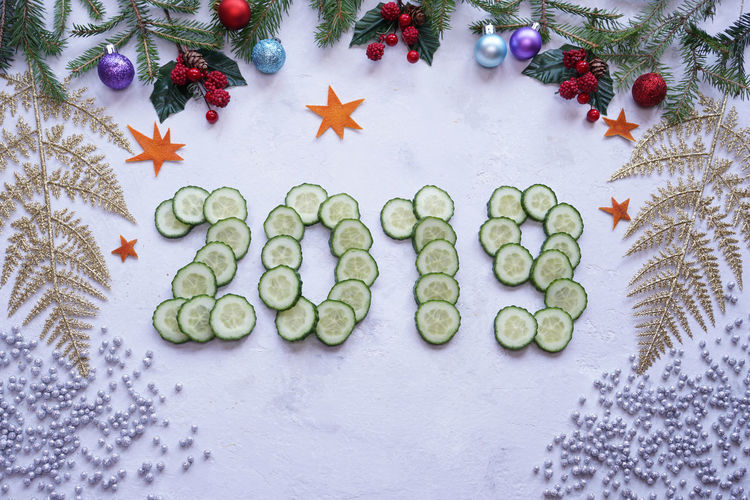 Directly above shot of new year sign made from cucumber slices surrounded with decorations
