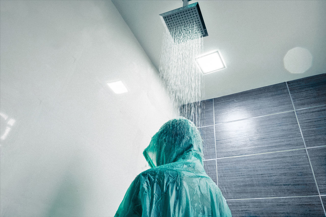 Low Angle View Of Boy Wearing Raincoat While Standing Below Shower In Bathroom