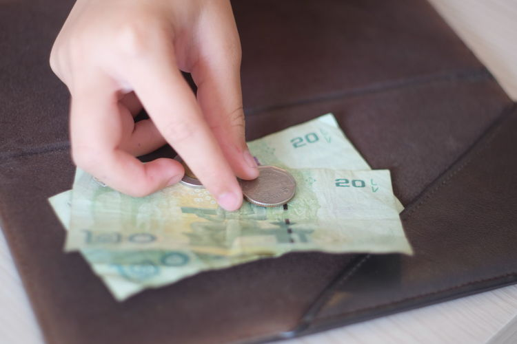 Cropped hand of person touching currency