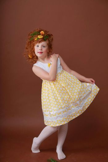 Portrait of girl in dress dancing against brown background