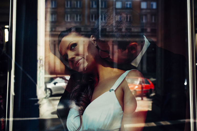 Portrait of young woman seen through glass window