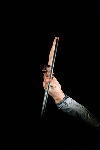 Circus Aggression  Arms Raised Black Background Body Part Copy Space Hand Holding Human Arm Human Body Part Human Hand Human Limb Indoors  Limb Music One Person Samurai Single Object Studio Shot Sword Weapon Young Adult