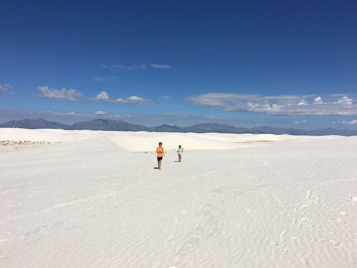 Siblings running on white sand against blue sky