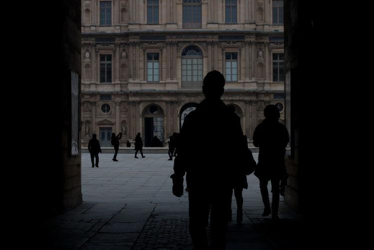 Rear view of silhouette people walking on footpath