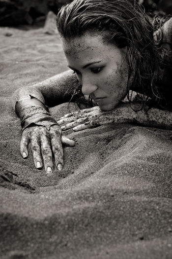 Close-up of muddy woman lying on sand at beach