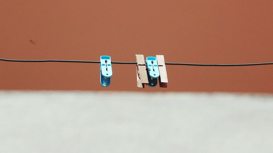 Clothespins On Clothesline Against Orange Background