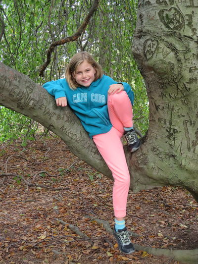Full length portrait of happy girl sitting on tree trunk