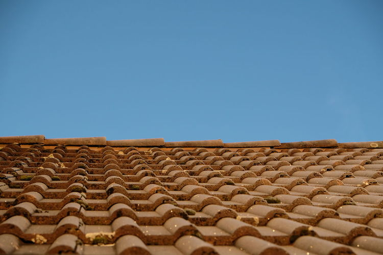 roof tiles against clear blue sky Blue Sky Roof Rooftop Roof Tile Roof Tiles Tiles Tile No People Pattern In A Row Day Outdoors Brown Surface Level Sky Copy Space Clear Sky Blue Nature Architecture Built Structure Building Exterior Low Angle View House Building Selective Focus