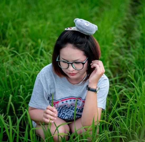 Woman wearing eyeglasses crouching on field against sky