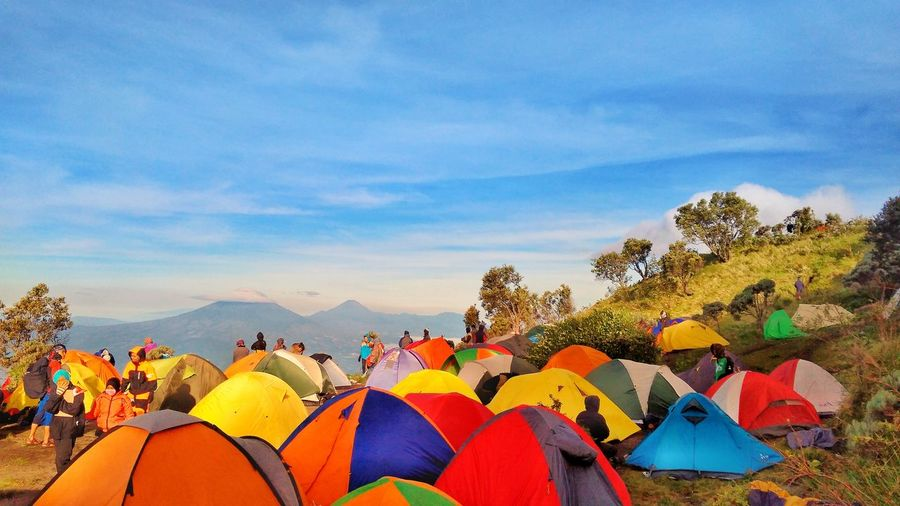 Tents And People On Mountains Against Sky