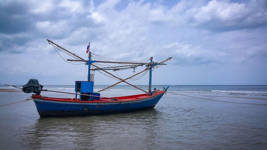 Fishing boat on sea against sky