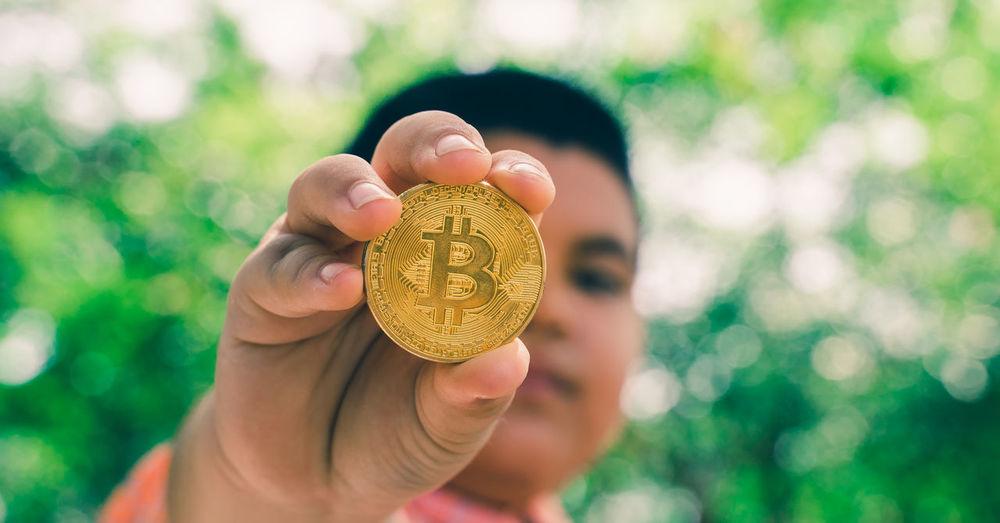 Close-up of man holding bitcoin