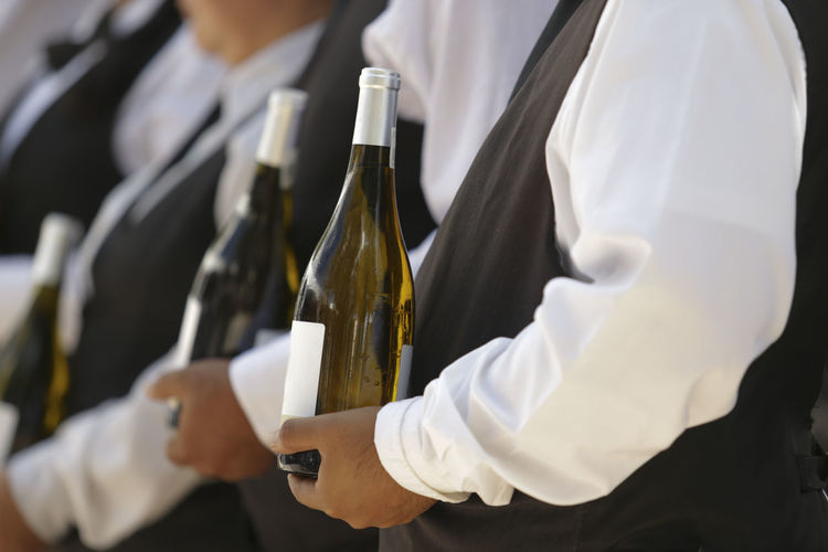 Close-up of hand holding wine bottles