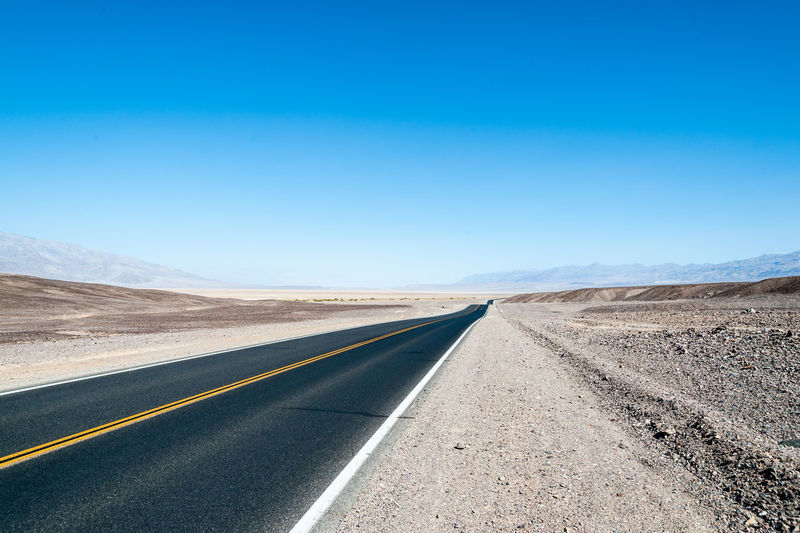 Empty road against clear blue sky