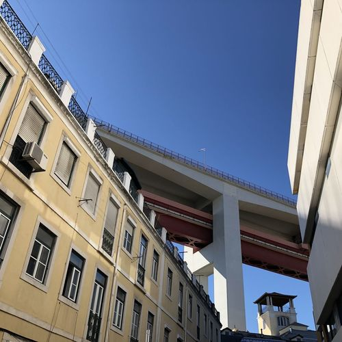 Low angle view of bridge over residential neighbourhood in Lisbon, Portugal Lisbon Portugal Architecture Building Exterior Built Structure Low Angle View Building Sky Day Nature No People Sunlight Clear Sky Residential District City Outdoors Window Blue Balcony Copy Space Apartment