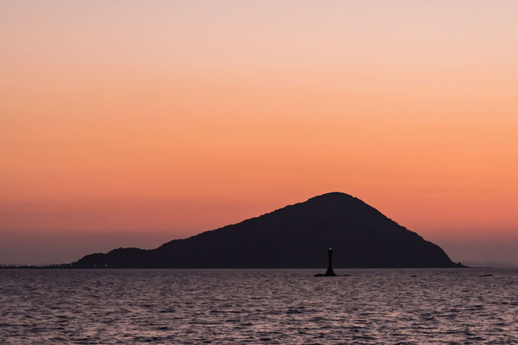 Silhouette island by sea against orange sky