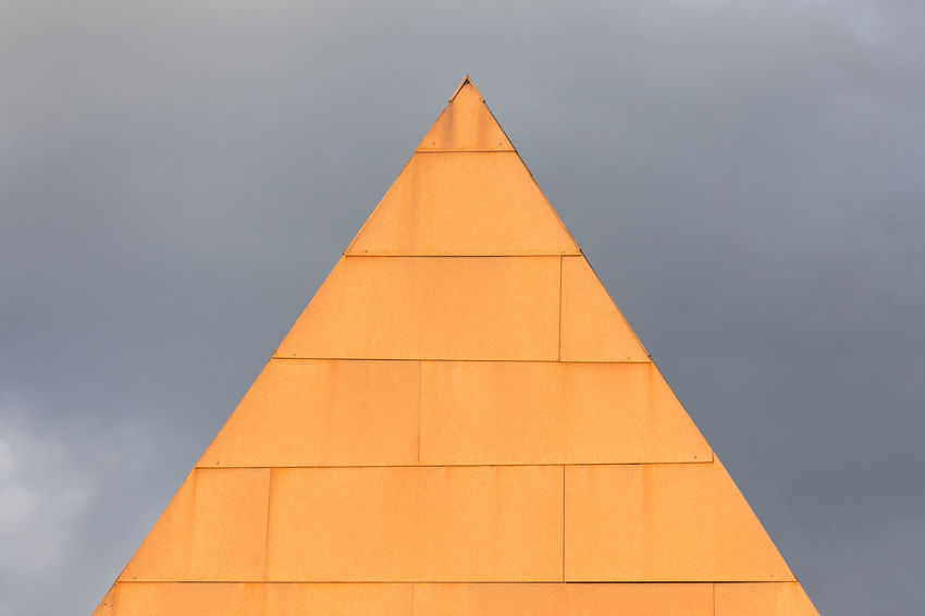 Close-up of rusty building exterior of a modern building illuminated by sun against gray sky Architecture Modern Moody Sky Sunlight Textured  Weather Weathered Abstract Architecture Building Exterior Built Structure Day Gray Illuminated Light Effect No People Orange Color Outdoors Pattern Rectangle Rusty Simplicity Sky Triangle Shape Wall - Building Feature