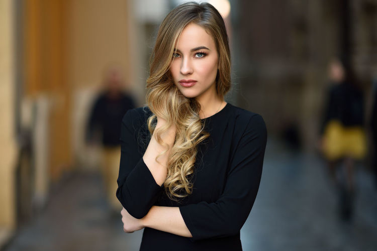 Blonde woman in urban background. Beautiful young girl wearing black elegant dress standing in the street. Pretty russian female with long wavy hair hairstyle and blue eyes. Hairstyles Looking At Camera Beautiful Woman Beauty Blond Hair Day Focus On Foreground Front View Hairstyle Lifestyles Long Hair One Person Outdoors Portrait Real People Russian Girl Standing Street Style Urban Wavy Hair Young Adult Young Women